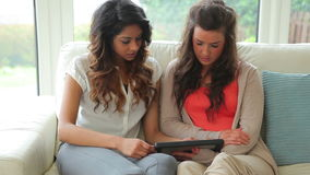 Women sitting on the couch holding a tablet PC stock video