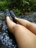 Women`s legs relax on the creek in the forest stock image