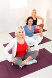Women sitting cross-legged on mat Royalty Free Stock Photos