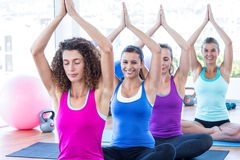 Women sitting in fitness studio with hands joined overhead Royalty Free Stock Images