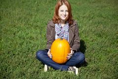 Woman sitting at green grass and keeping pumpkin. Stock Photography