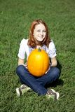 Women sitting at green grass and keeping pumpkin. Royalty Free Stock Photo
