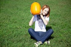 Women sitting at green grass and keeping pumpkin. Royalty Free Stock Photography