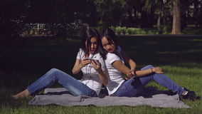 Women sitting on the lawn with green grass in the park. Two asian happy girls looking funny photo on smartphone. Smiling woman using mobile phone laughing stock video