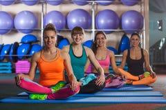 women sitting in lotus pose on mat at gym Stock Images