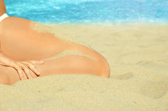 Women is sitting on the sand at the beach Royalty Free Stock Images