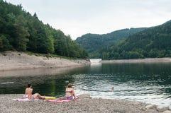 Women sitting in suit swim in border lake Royalty Free Stock Photos