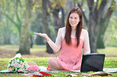 Women sitting on wooden mat and holds a sign on parkland. Royalty Free Stock Image