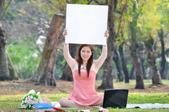 Women sitting on wooden mat and holds a sign at parkland. Stock Image