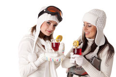 Women with skates and skis drink mulled wine. Stock Images