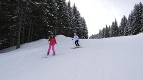 Women Skiers Ride One After Another On A Ski In The Mountains On A Forest Track. Shot front view in motion. Two women skiers skiing on the ski slope in a pine stock video
