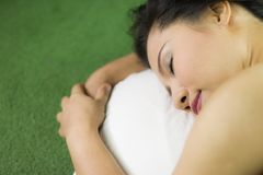 Women sleep on the green grass, a beautiful and dreamy Thai woman laying down on green grass, relaxing royalty free stock photo