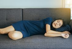 Women sleeping on sofa bed and grinding teeth,Female tiredness and stress at living room. Woman sleeping on sofa bed and grinding teeth,Female tiredness and royalty free stock photography