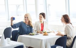Women with smartphone taking selfie at restaurant Stock Photo