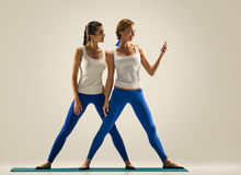Women with smartphone. yoga in pair Stock Photos