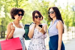 Women with smartphones and shopping bags in city royalty free stock photography