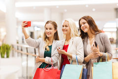 Women with smartphones shopping and taking selfie. Sale, consumerism, technology and people concept - happy young women with smartphones and shopping bags taking Stock Photography