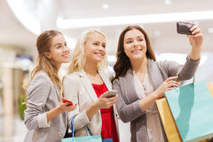 Women with smartphones shopping and taking selfie Stock Photos