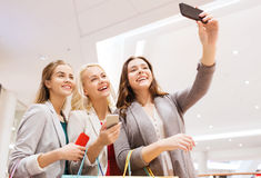 Women with smartphones shopping and taking selfie Stock Image