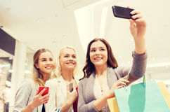 Women with smartphones shopping and taking selfie. Sale, consumerism, technology and people concept - happy young women with smartphones and shopping bags taking royalty free stock photography