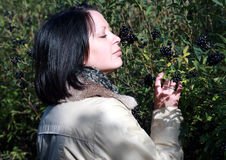 Women smells berries currant on park Royalty Free Stock Photos