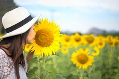 Women smells sunflower in nature. Relax Royalty Free Stock Photos