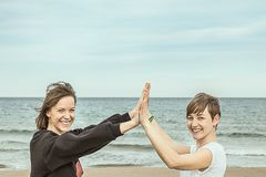 Women smiling on the beach, putting their hands together royalty free stock photography