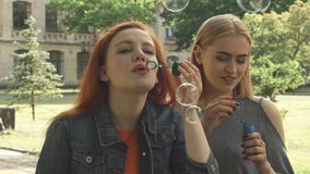 Two girls blowing bubbles outdoors stock video footage
