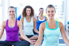 Women smiling while doing easy pose in fitness studio Royalty Free Stock Images