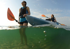 Women smiling Two women in blue kayak royalty free stock image
