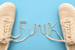 Women sneakers with laces in funk text. New women sneakers with laces in funk text. Flat lay on blue background stock photo