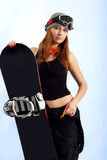 Women snowboarder in the goggles. Snowboarder in a goggles holding his board Royalty Free Stock Photography