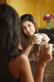 Women Socialize in Kitchen. Young Hispanic woman with coffee chat in kitchen Stock Photography