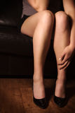 Women in sofa. Young woman / girl sitting lonely on a leather couch. Holding her hand at her leg royalty free stock images