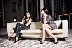 Women on sofa. Two glamorous women sitting on a comfortable sofa in a luxurious house Stock Image