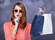 Women with sopping bags. Redhead woman with sopping bags. Studio shot stock photo