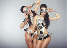 Women in Sparkling Cosmic Cyber Costumes Gesturing Stock Photo