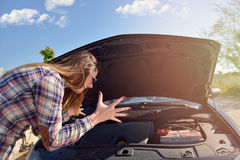 Women spection She opened the hood Broken car on the side See engines that are damaged or not. royalty free stock image