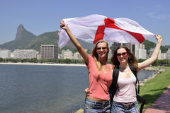 Women sport fans holding the England flag in Rio de Janeiro.ound. Couple of female sport fans holding the England flag in Rio de Janeiro with Christ the Stock Image