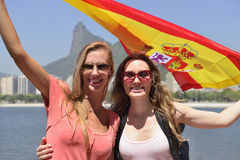 Women sport fans holding the Spanish flag in Rio de Janeiro.ound. Couple of female sport fans holding the Spanish flag in Rio de Janeiro with Christ the Royalty Free Stock Photo