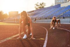 Women sprinters at starting position ready for race on racetrack. Women sprinters at starting position ready for race on racetrack Royalty Free Stock Photography