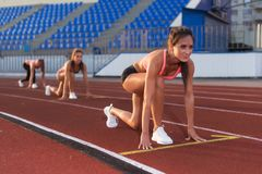 Women sprinters at starting position ready for race on racetrack. Women sprinters at starting position ready for race on racetrack Royalty Free Stock Photo