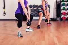 Women squatting with kettlebells Stock Photos