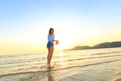 Women stand and hold hat on the beach between sunset. royalty free stock photos