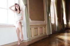 Women stand near of window in old house. In white dress and she looks like italian women Royalty Free Stock Image