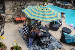 Women standing around patio table beside swimming pool with nice outdoor furniture - top view Tulsa OK Stock Photos