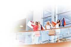 Women standing on balcony. Four women with shopping bags standing on balcony at mall Royalty Free Stock Photo