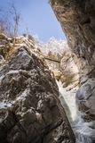 Women standing on bridge over frozen icy waterfall in Baerenschu. Young women standing on bridge high over the big frozen icy waterfall in snow covered gorge Stock Photos
