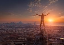 Women standing on the cliff towards the cityscape and setting su Stock Photography