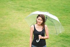 Women standing holding umbrellas in the lawn stock photography